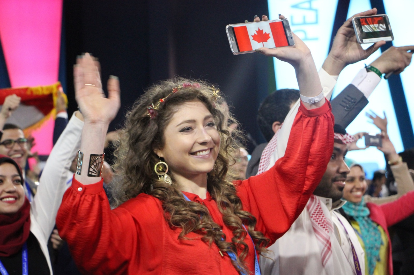 Kelly wearing a red blouse and gold headpiece waving in a crowd holding the canadian flag